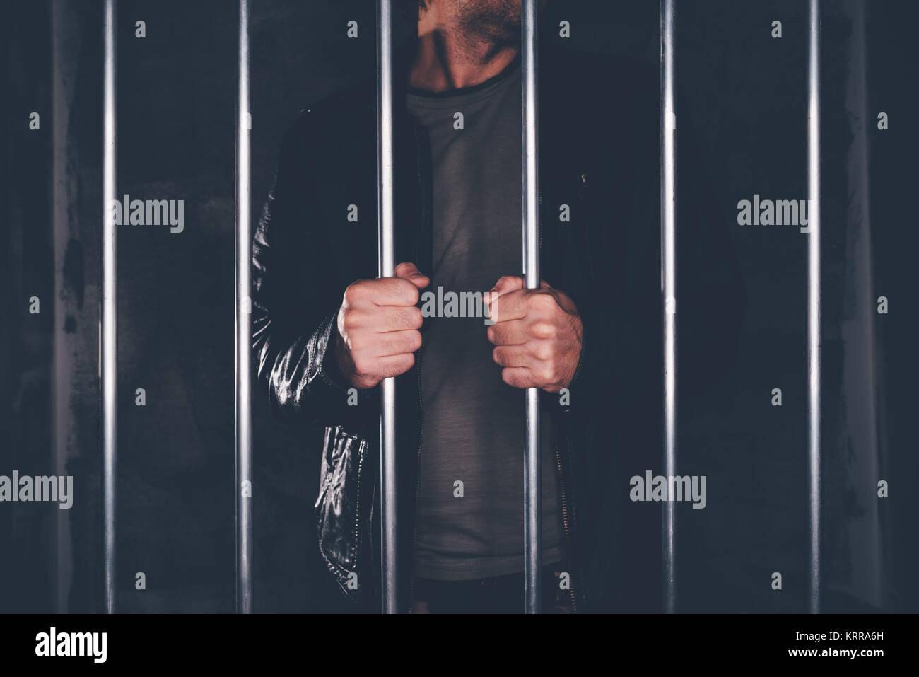 Man behind prison bars. Arrested criminal male person imprisoned. - Stock Image
