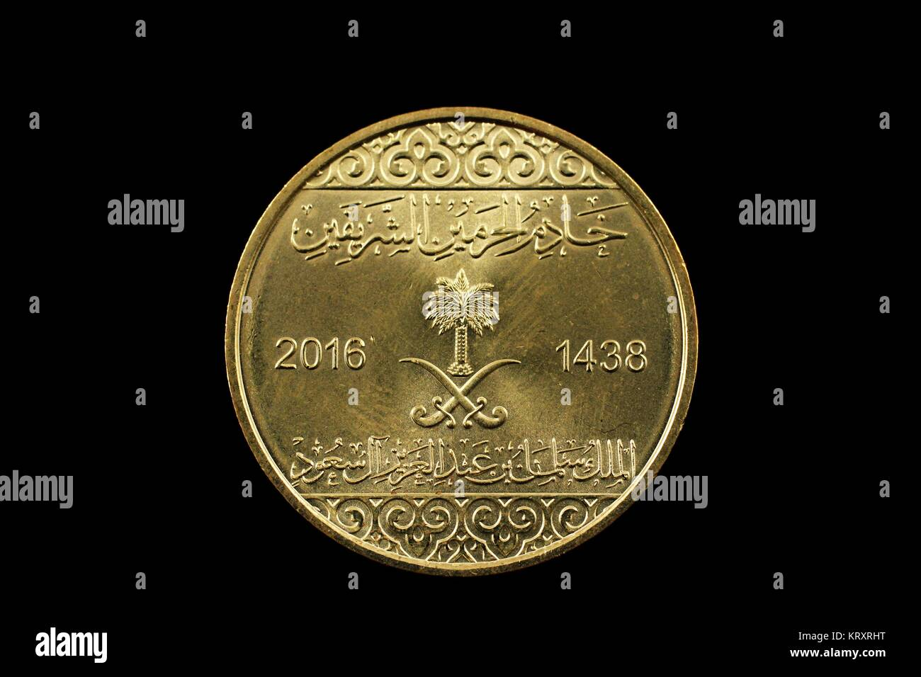 A super macro image of a gold saudi arabian coin isolated on a black background - Stock Image