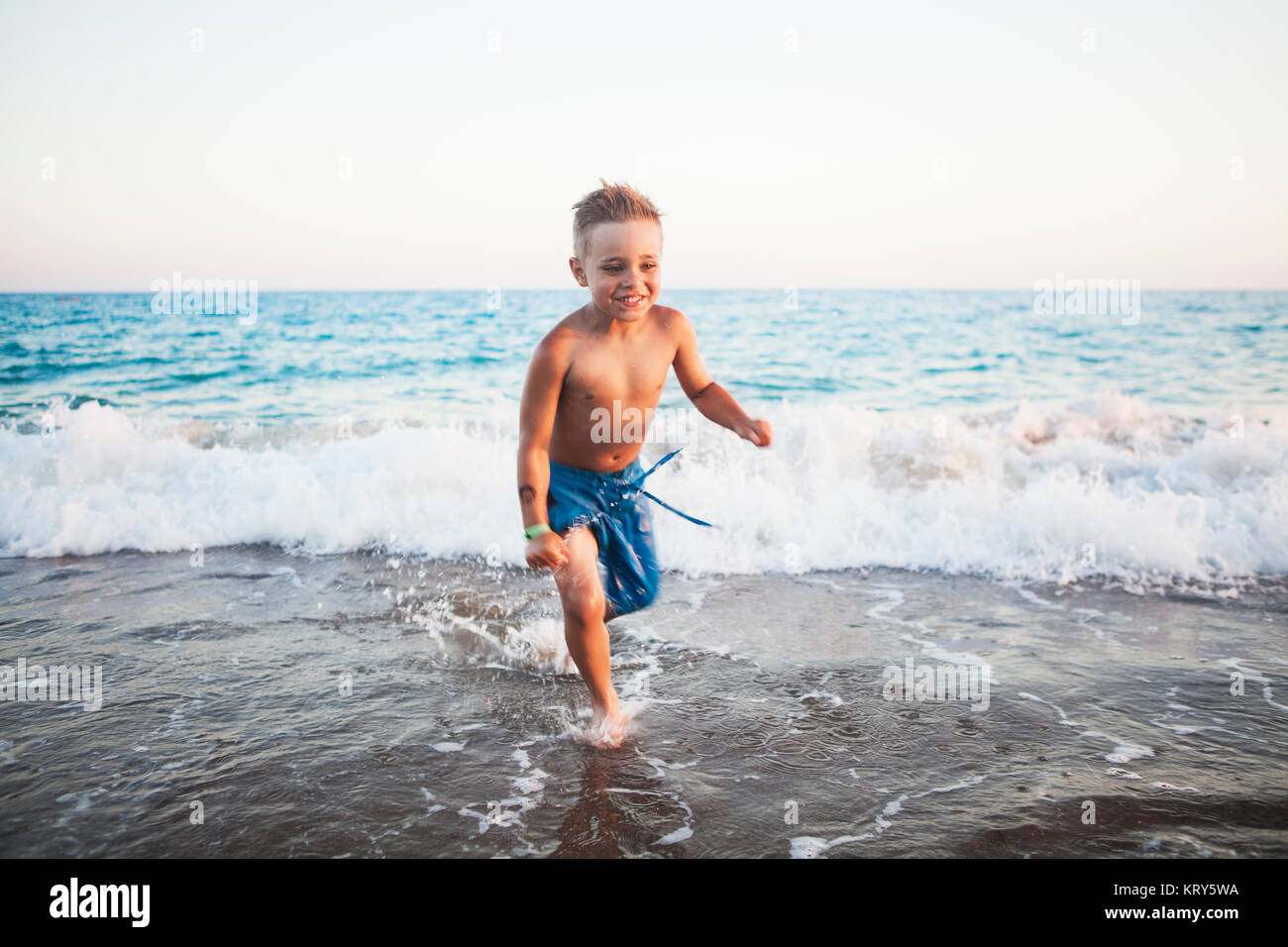 A young boy playing in the surf at a beach in Turkey - Stock Image