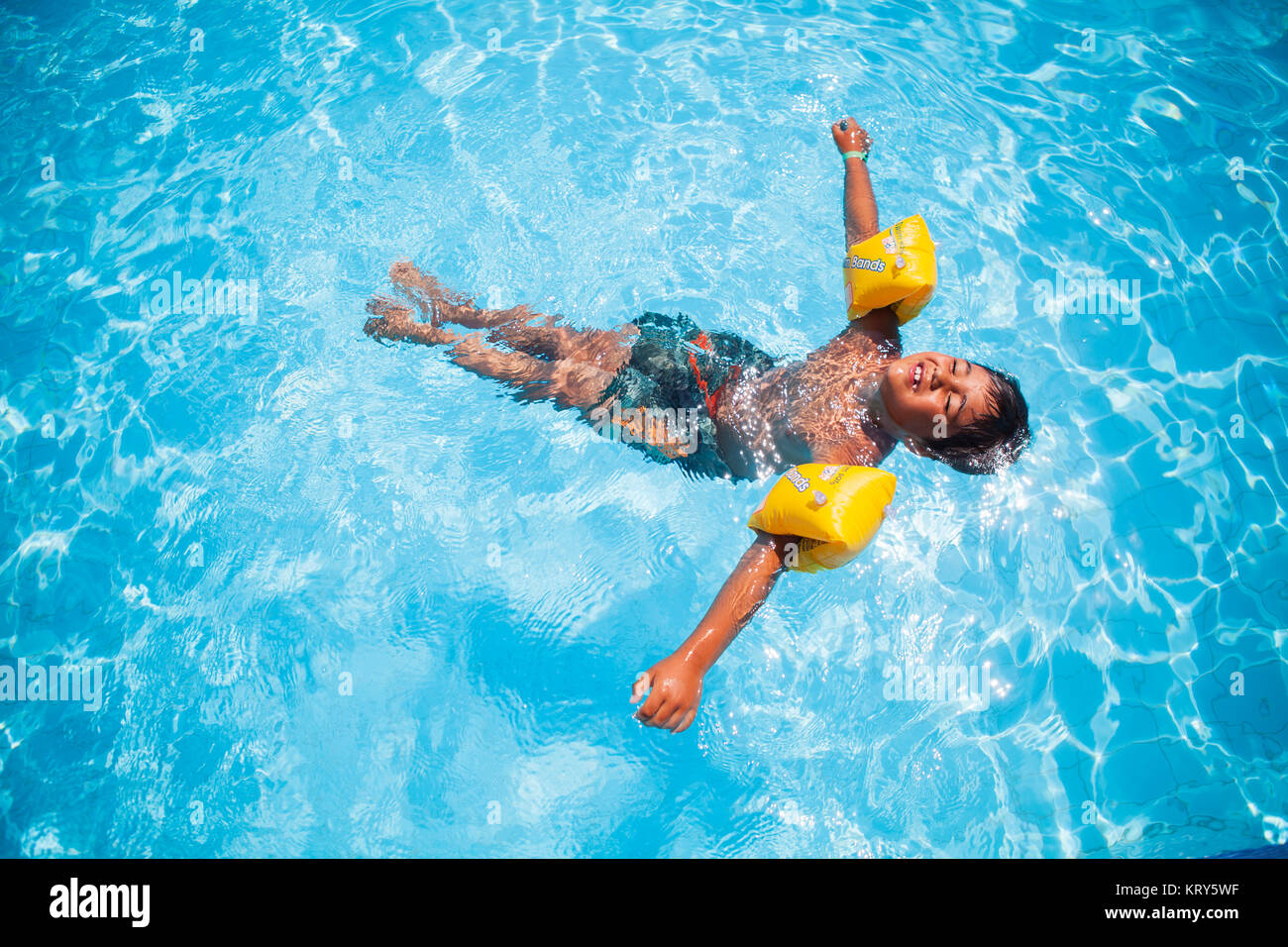A boy wearing water wings floating in a pool - Stock Image