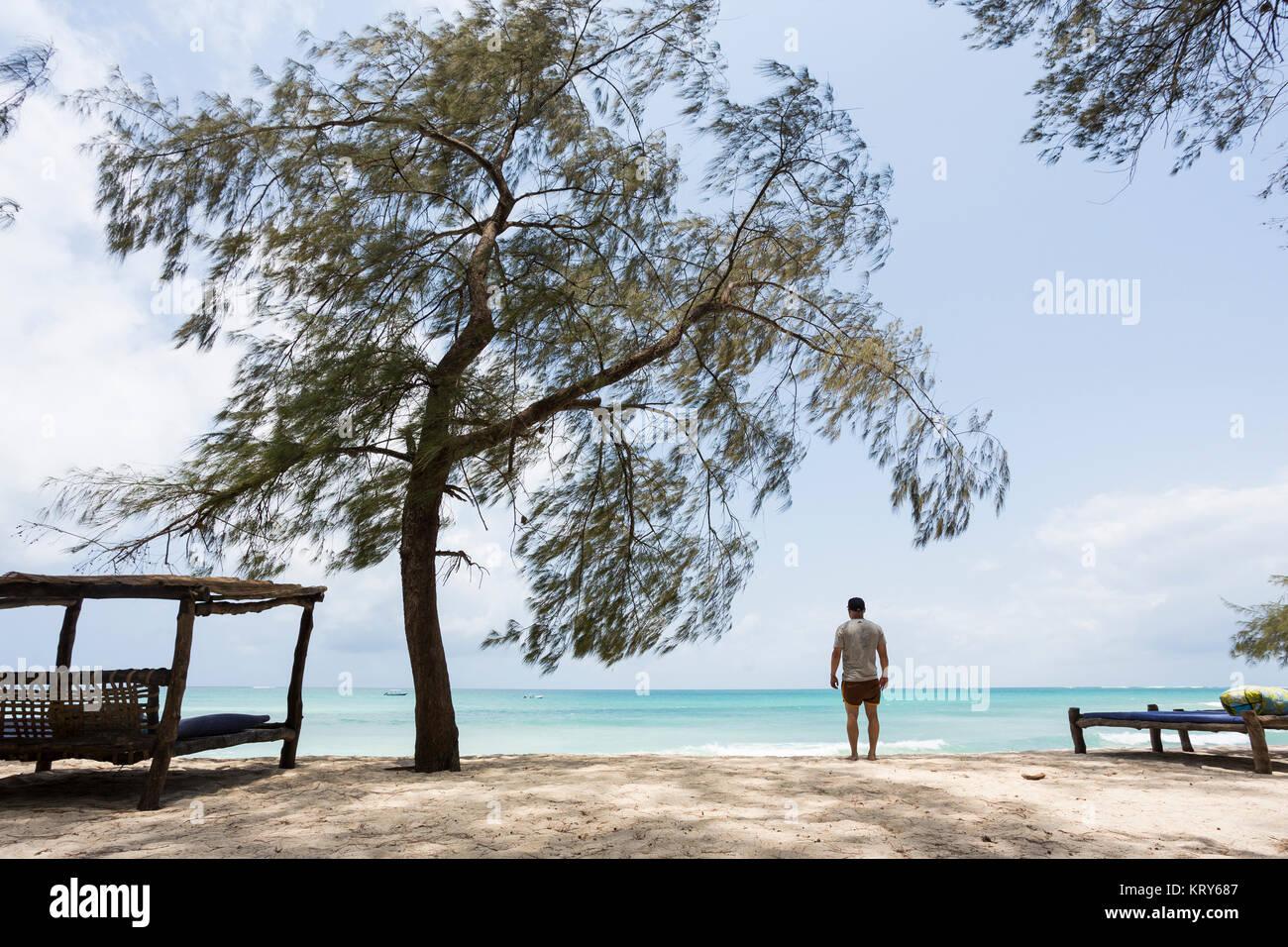 Man standing on Diani Beach, Kenya - Stock Image