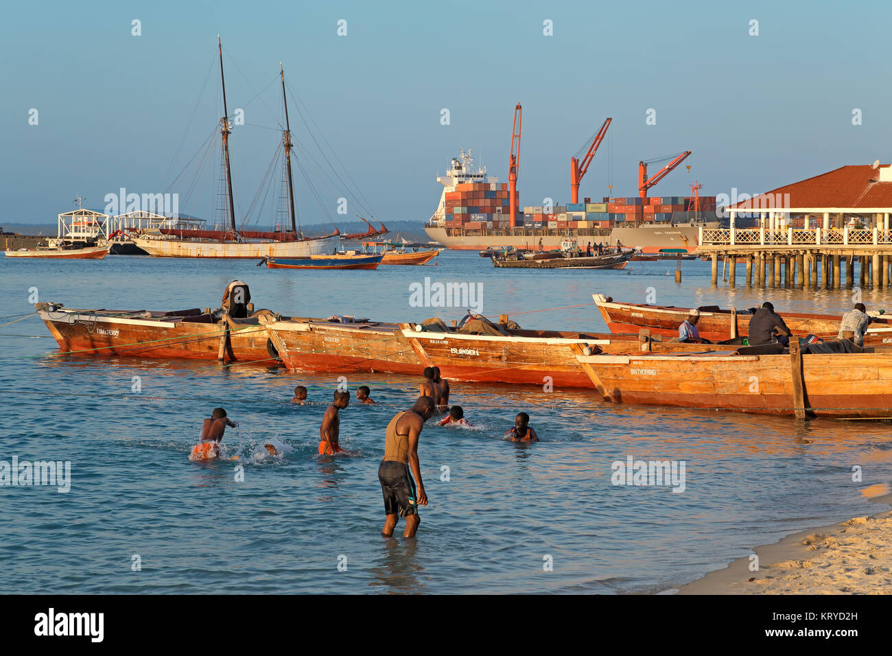 STONE TOWN, ZANZIBAR, TANZANIA - OCTOBER 29, 2014: Boats anchored and children playing in the shallow water of the - Stock Image