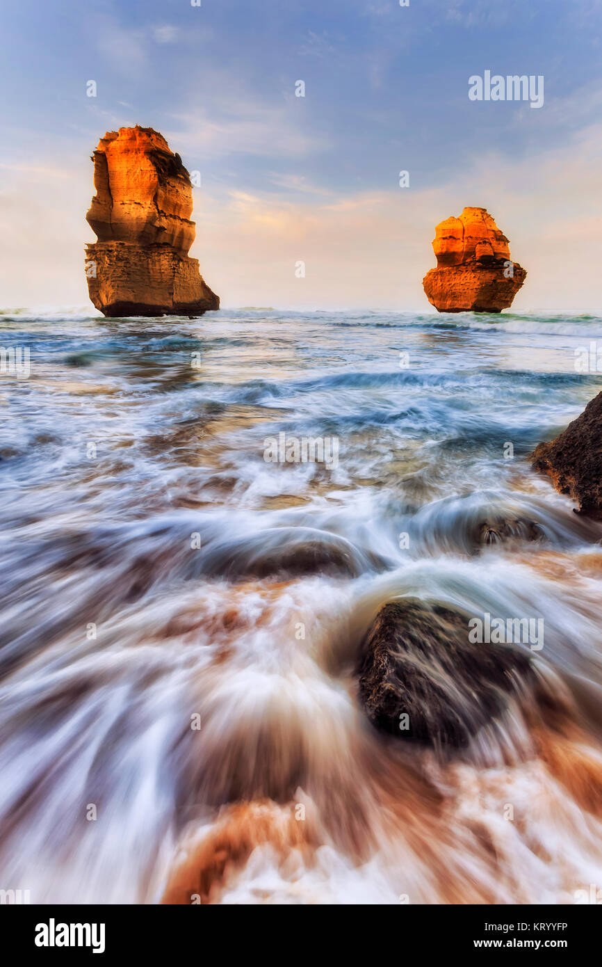 Two limestone eroded disconnected apostle rocks off Gibson Steps sandy beach on Twelve Apostles marine park at sunrise. - Stock Image