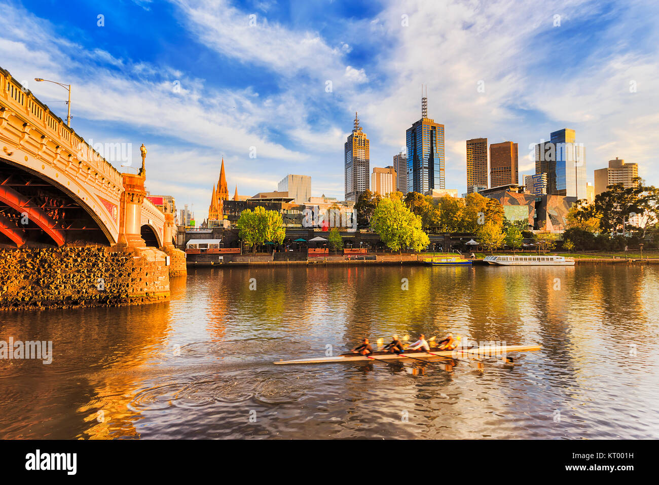 Golden sunlight and morning hour over Melbourne city CBD landmark high-rise towers on waterfront of Yarra river - Stock Image