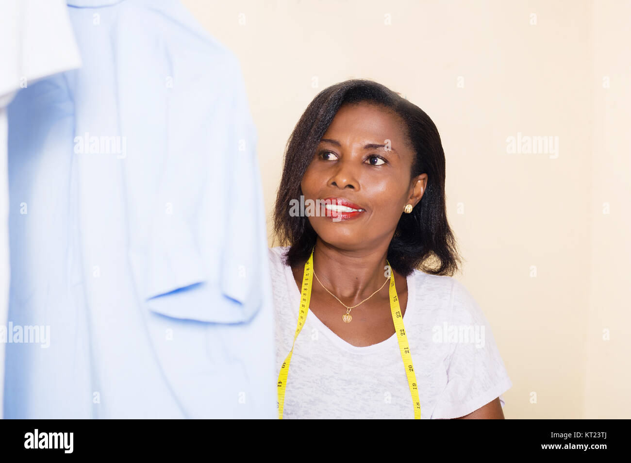 Close-up of a seamstress arranging shirts in the studio - Stock Image
