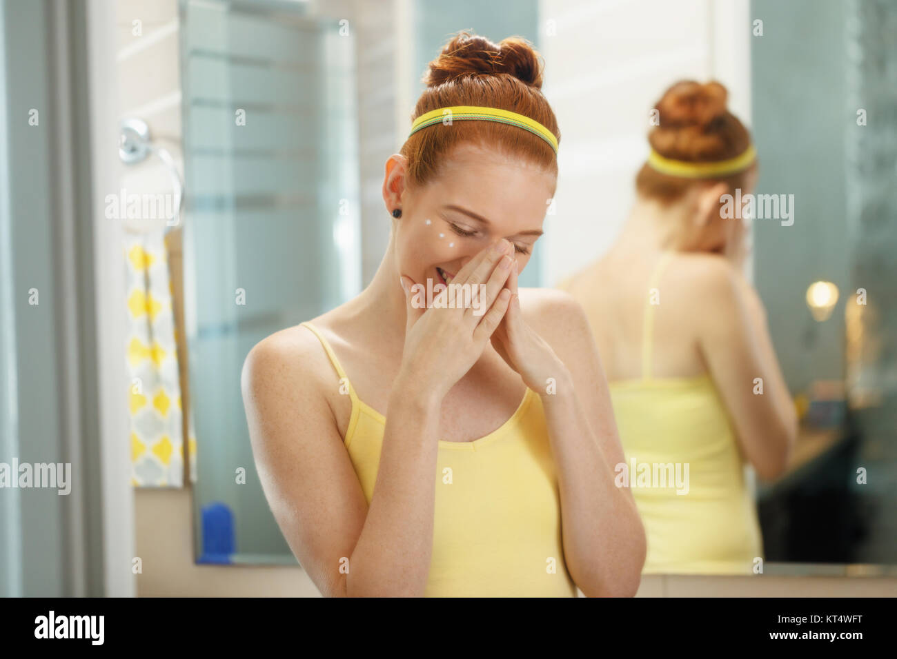 Redhead girl applying beauty cream in home bathroom at morning. Young woman taking care of her skin, looking and - Stock Image