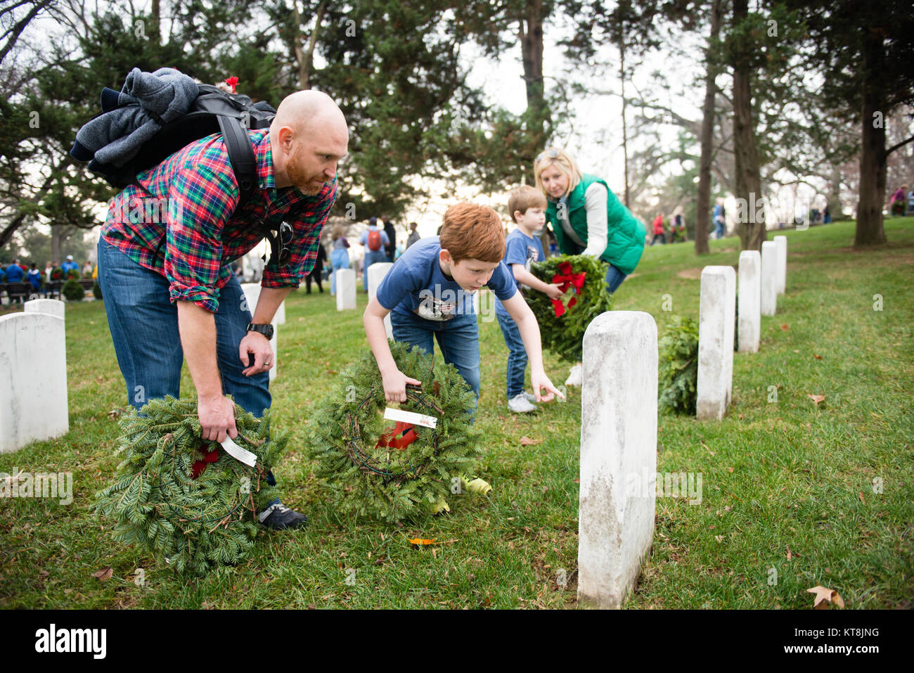 From the left, Kevin; Thomas, 8; Ben, 5; and Bethany Roshak, all from Ashburn, Va., place wreaths on headstones - Stock Image