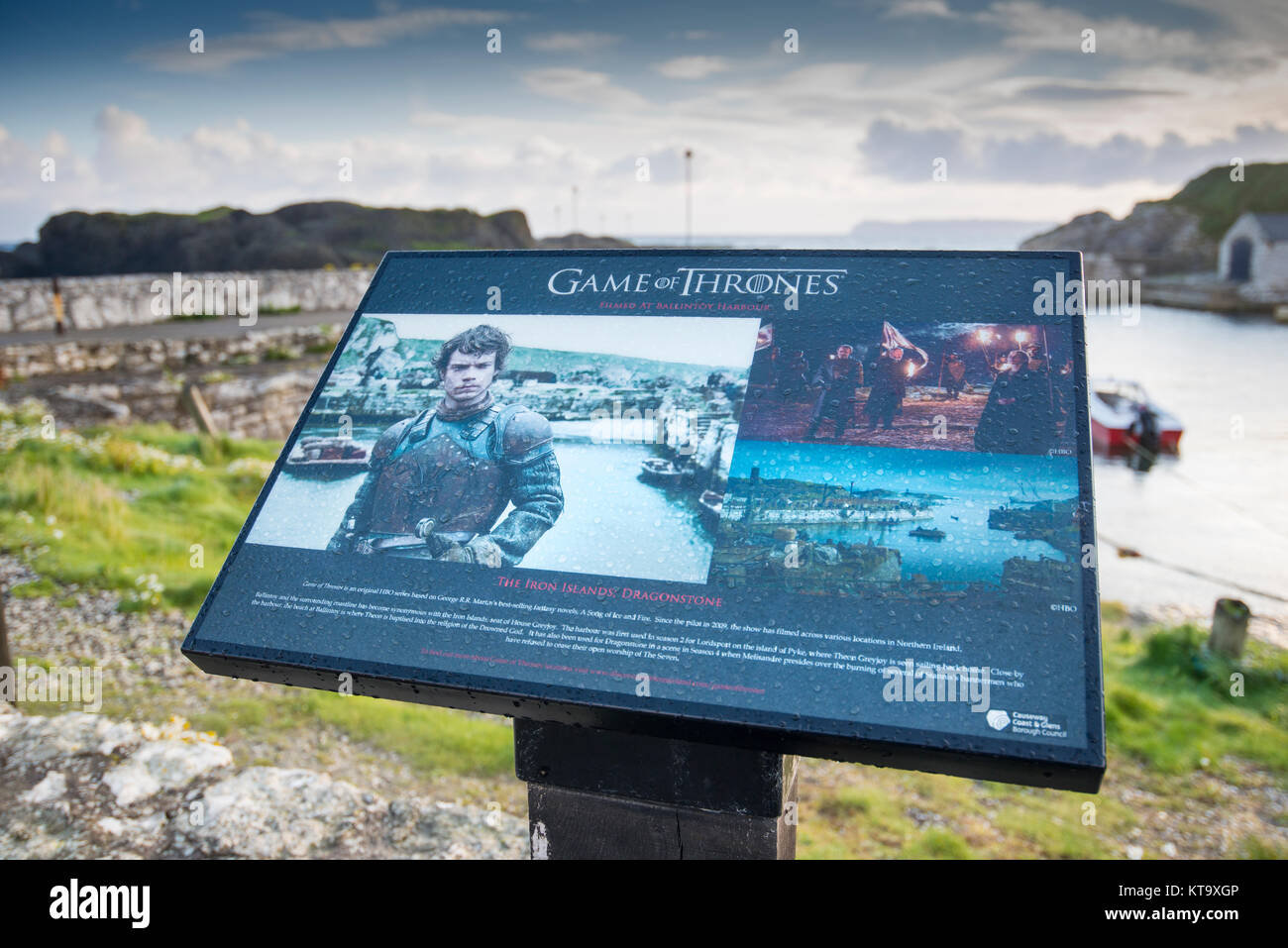 Visitor information board at Ballintoy Harbour in County Antrim, Northern Ireland, which was used as a location - Stock Image