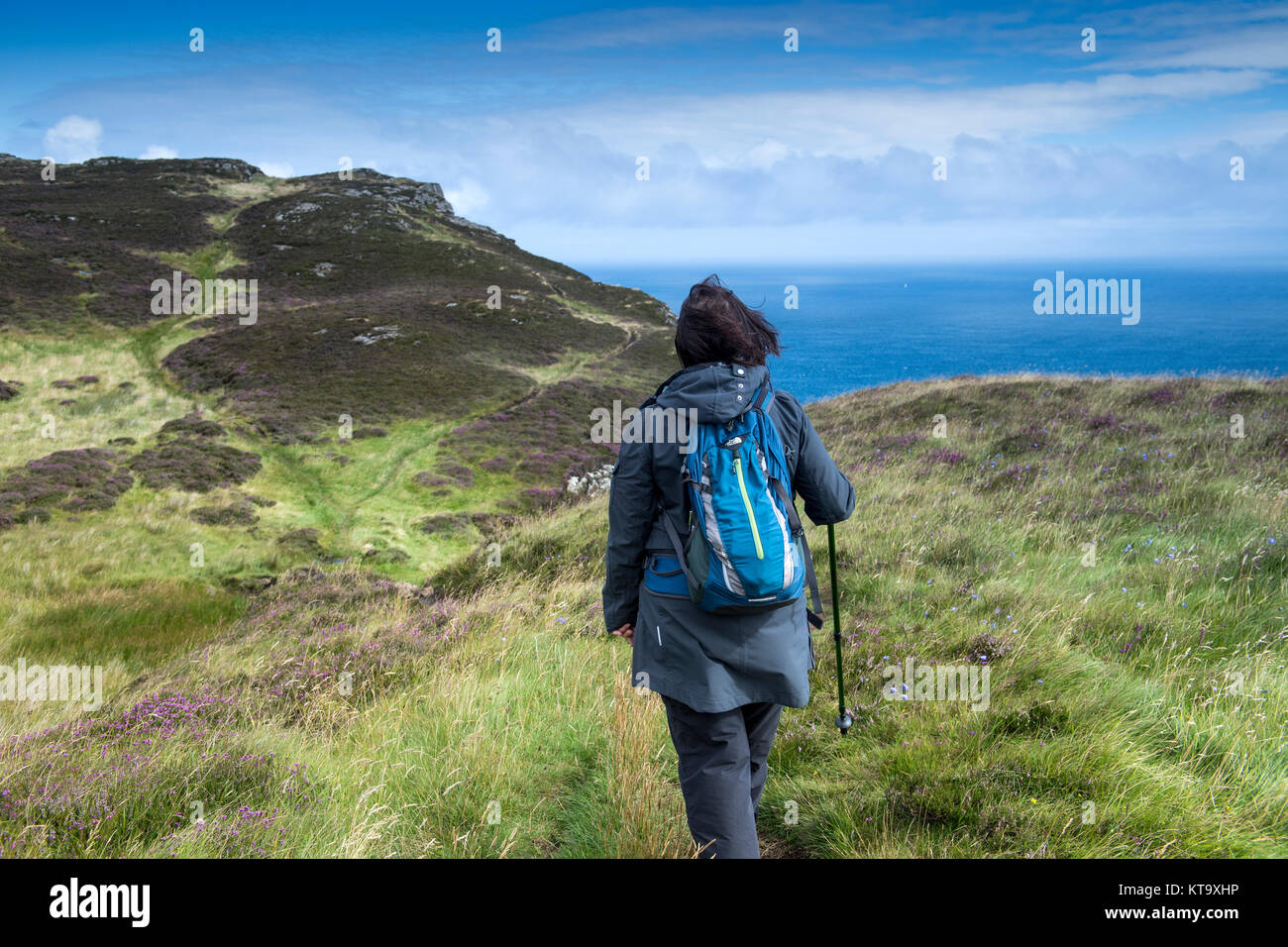 Woman hiking on the top of Fair Head in County Antrim, Northern Ireland - Stock Image