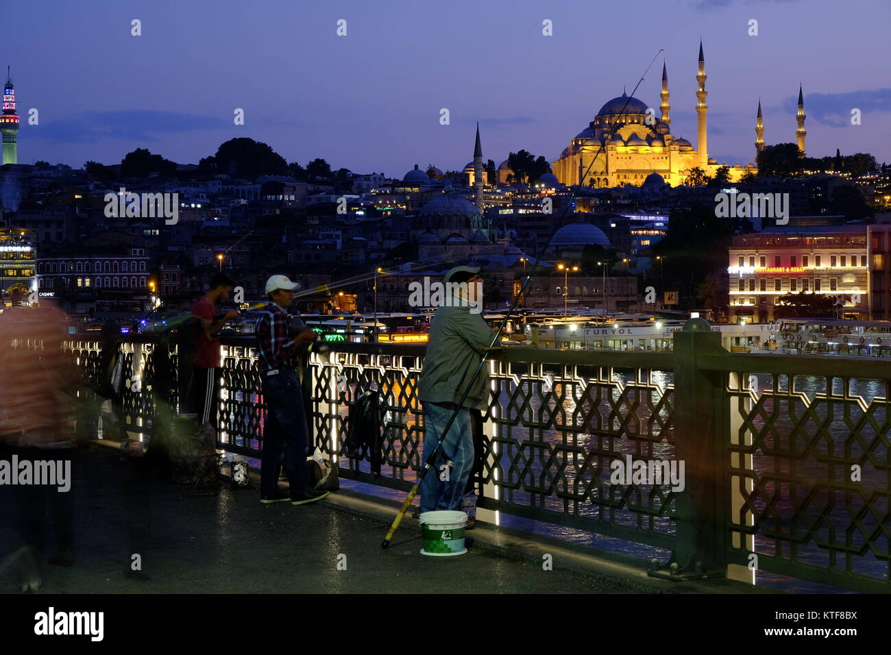 Fishermen fishing from the Galata bridge in Istanbul at the evening in Turkey - Stock Image