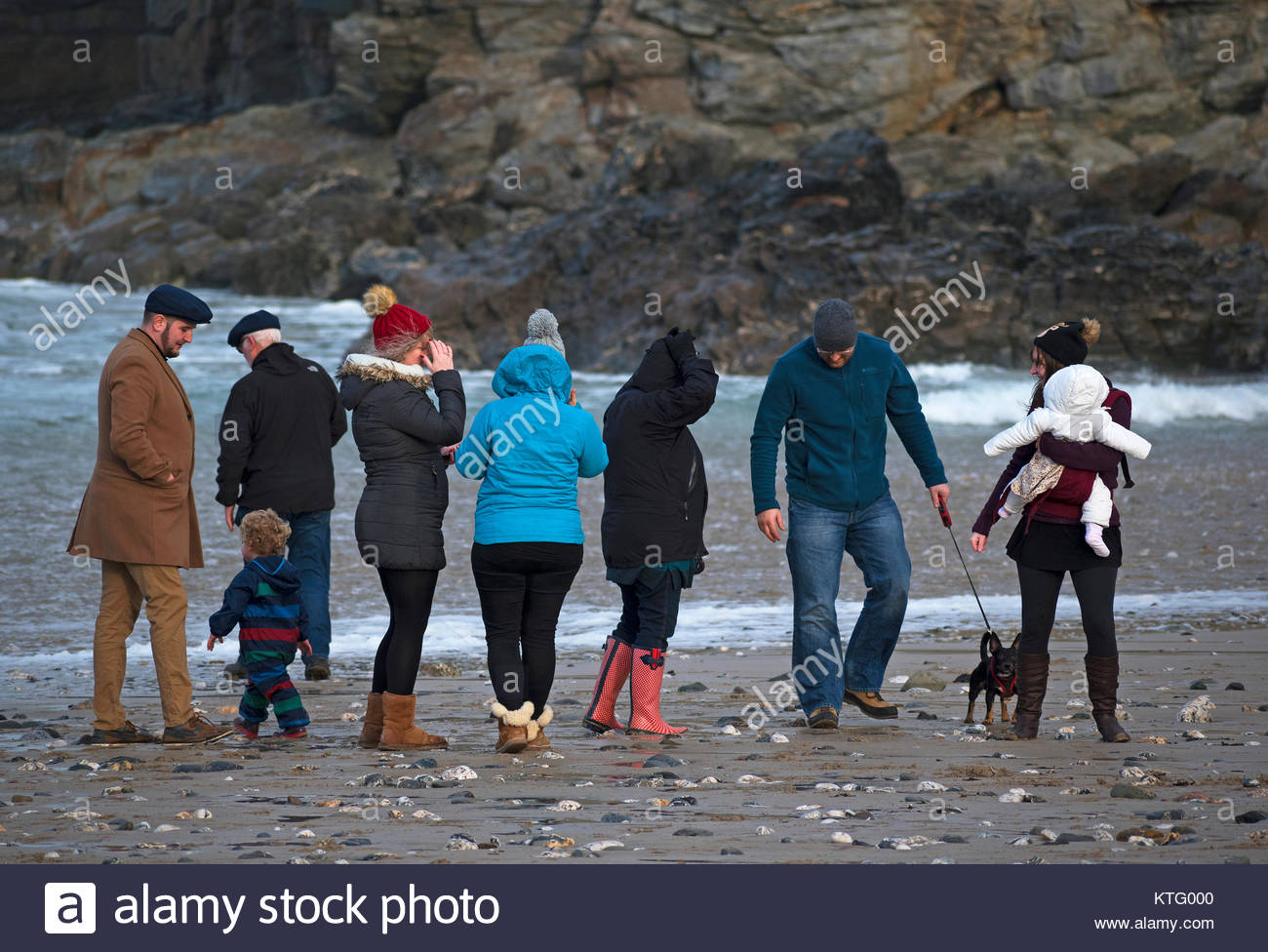 Porthtowan, Cornwall, UK. Christmas Day 25th December 2017. Family take a bracing pre lunch walk on the beach at - Stock Image