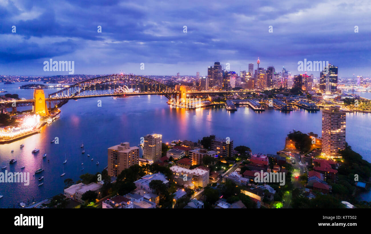 Sydney city CBD from Blues Point and North Sydney at sunset with bright illiumination of famours landmarks around - Stock Image