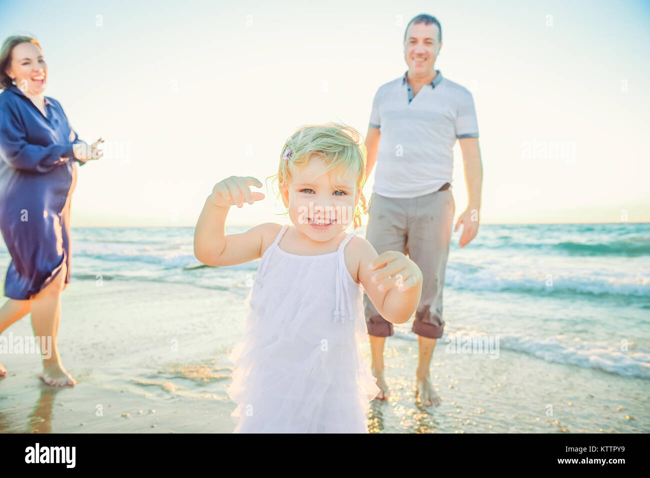 Laughing Baby girl running forward with smiling parents on the background. Happiness and harmony in family life. - Stock Image