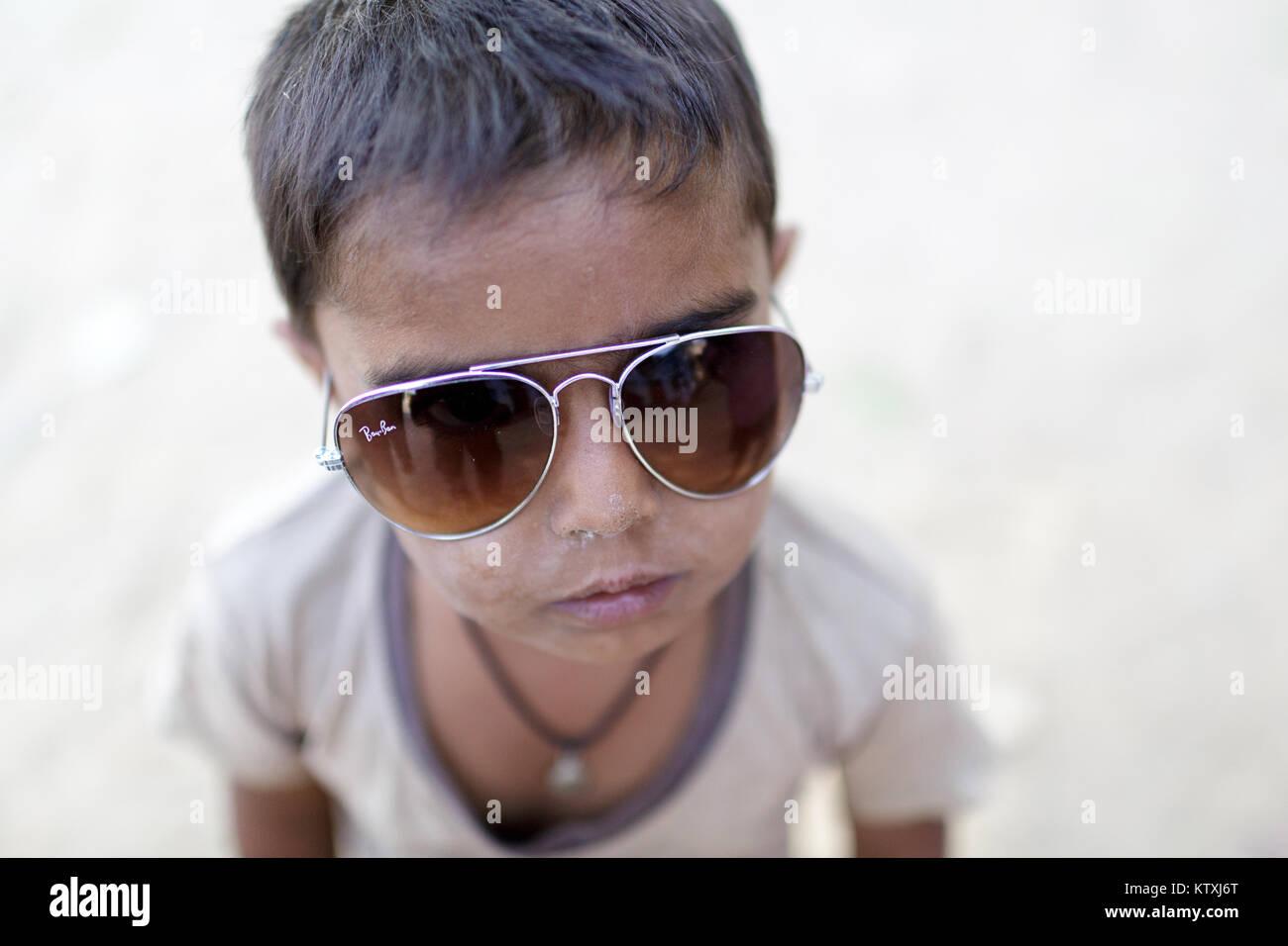 Small indian boy wearing oversized sunglasses, Village near Pushkar, Rajasthan, India. Stock Photo