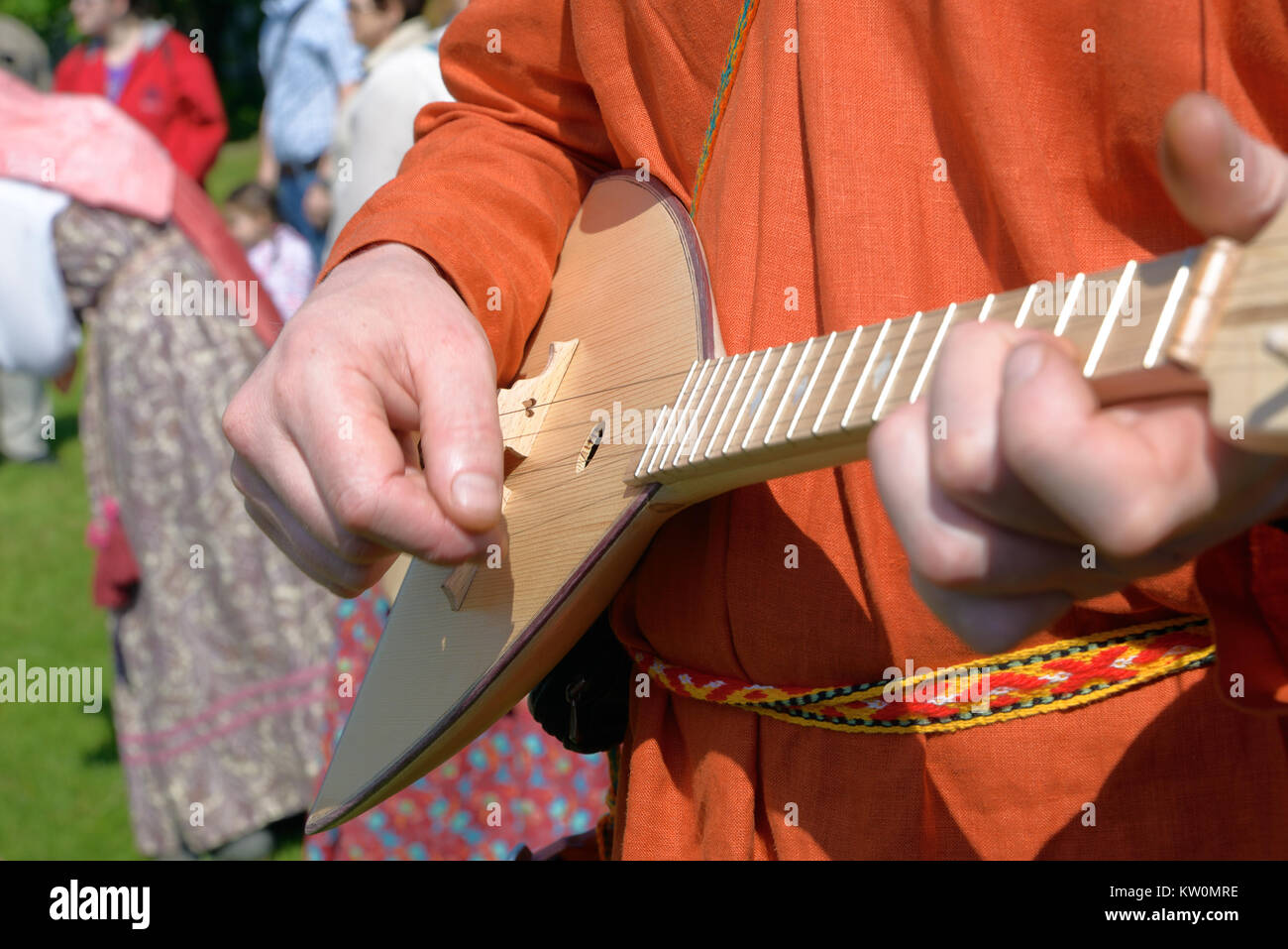 Balalaika in hands of the man dressed in a national Russian suit, close up - Stock Image