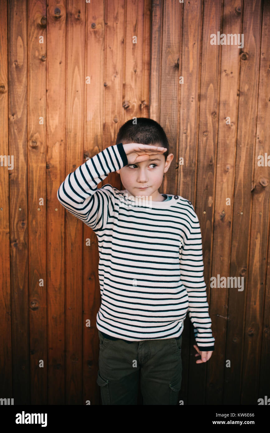 6 years old boy holding his hand on his forehead - Stock Image