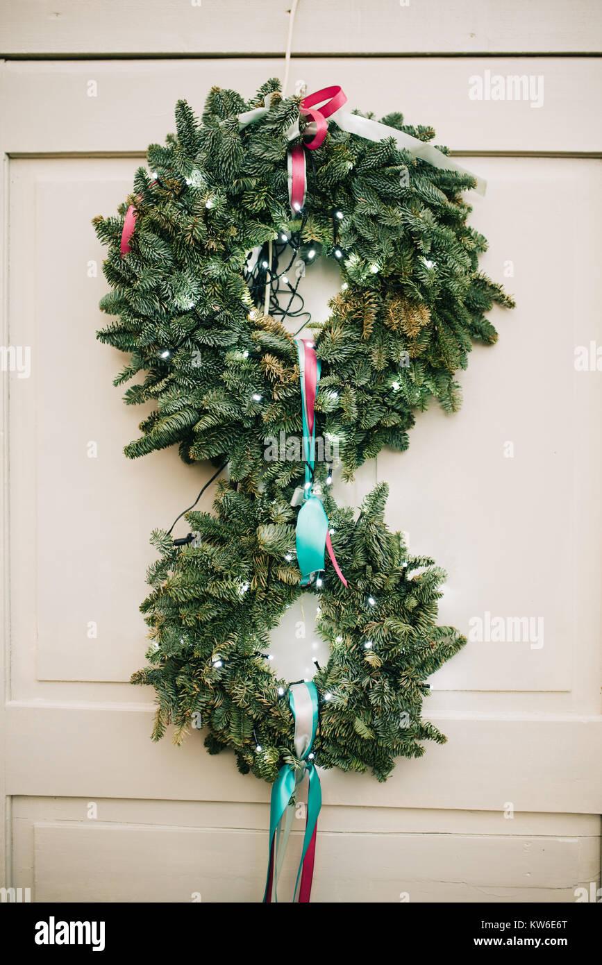 Two christmas wreats on white wooden door - Stock Image