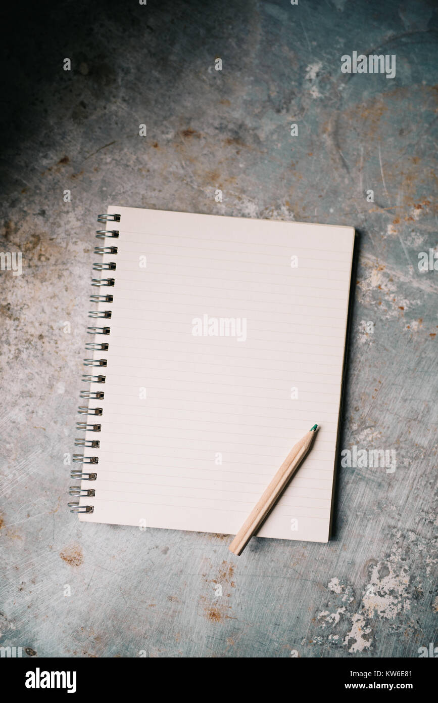Blank white notepad on old metal surface - Stock Image