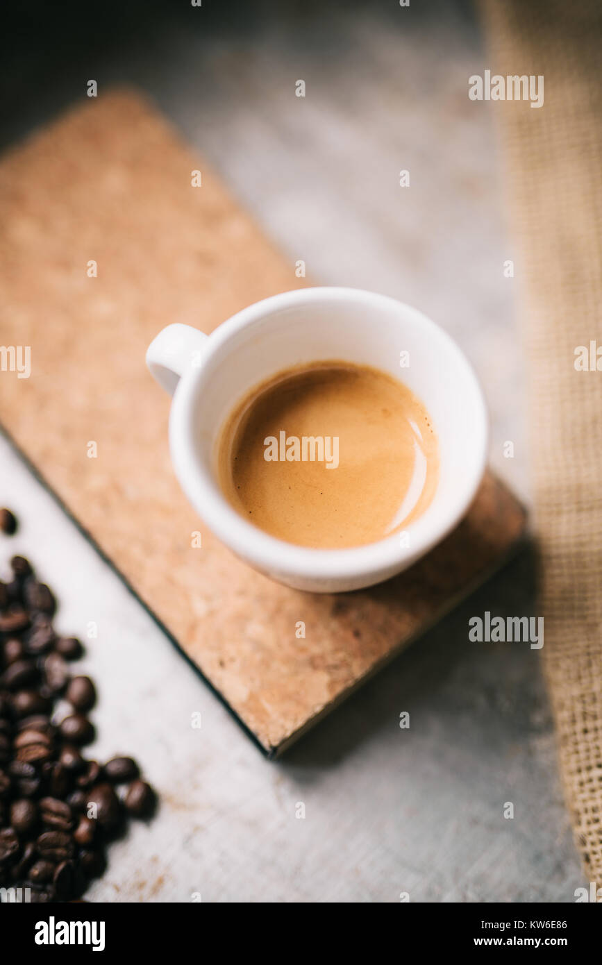 Fresh espresso and brown notepad on old metal surface - Stock Image