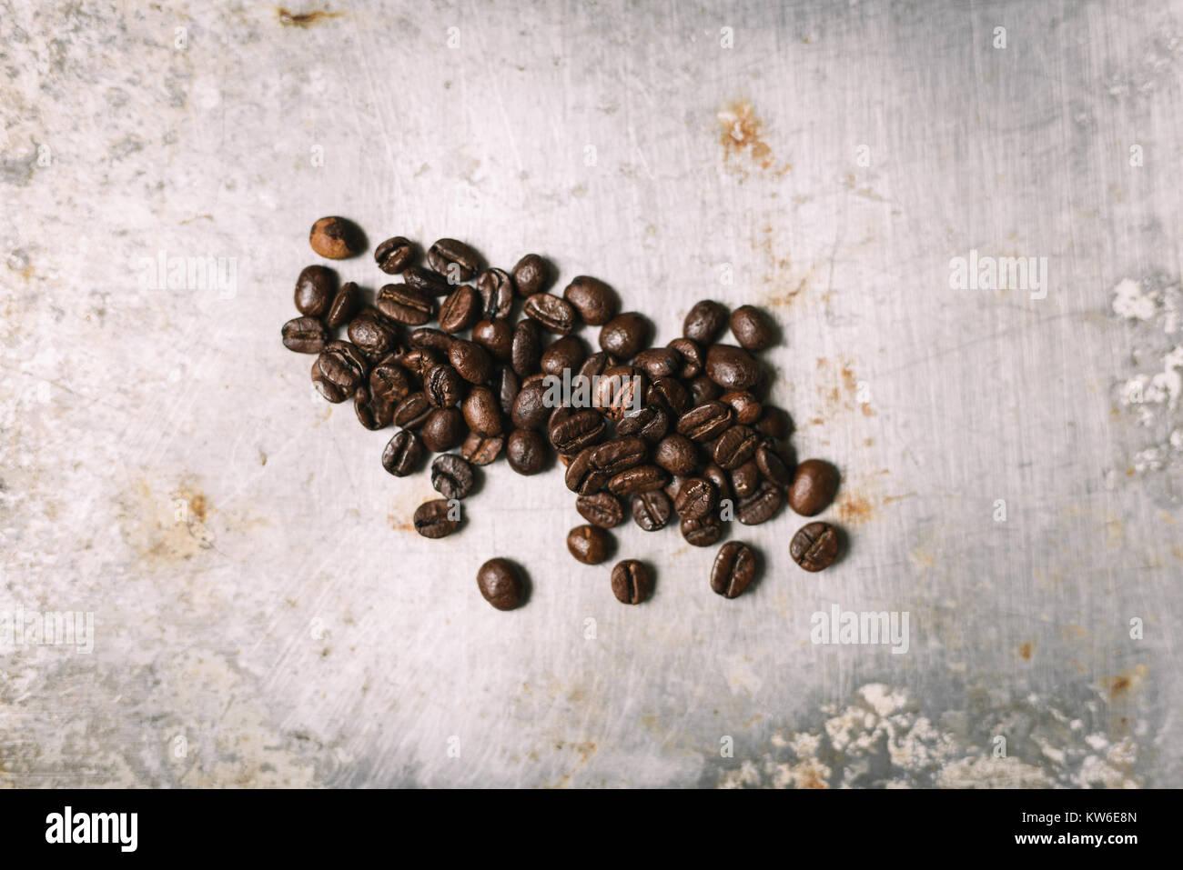 Roasted coffee bean on vintage metal surface - Stock Image