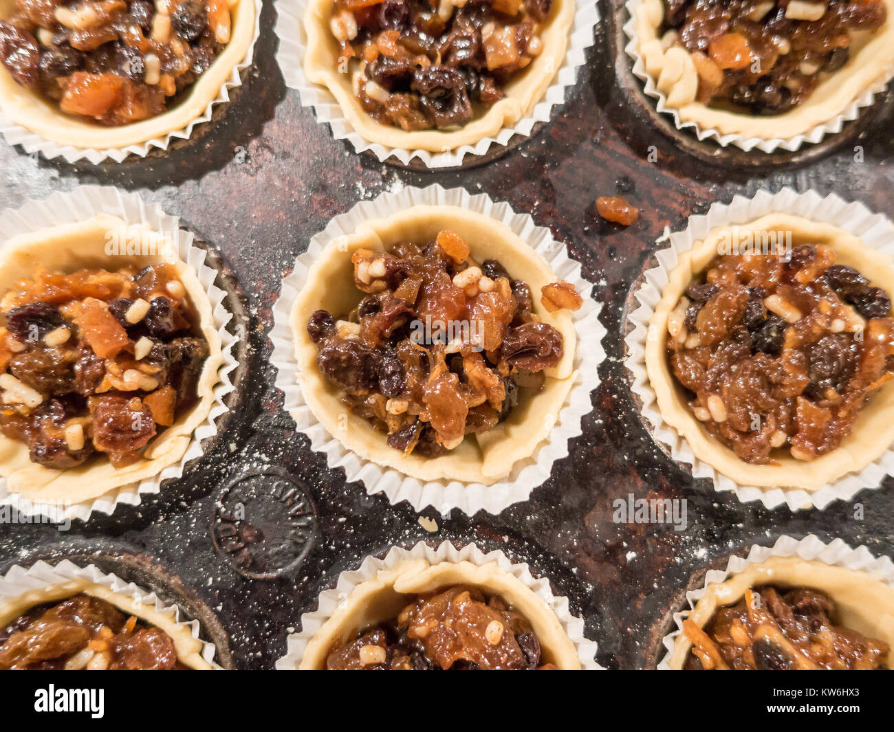 making-mince-pies-mince-pies-in-a-baking-tray-circles-of-pasty-have-KW6HX3.jpg
