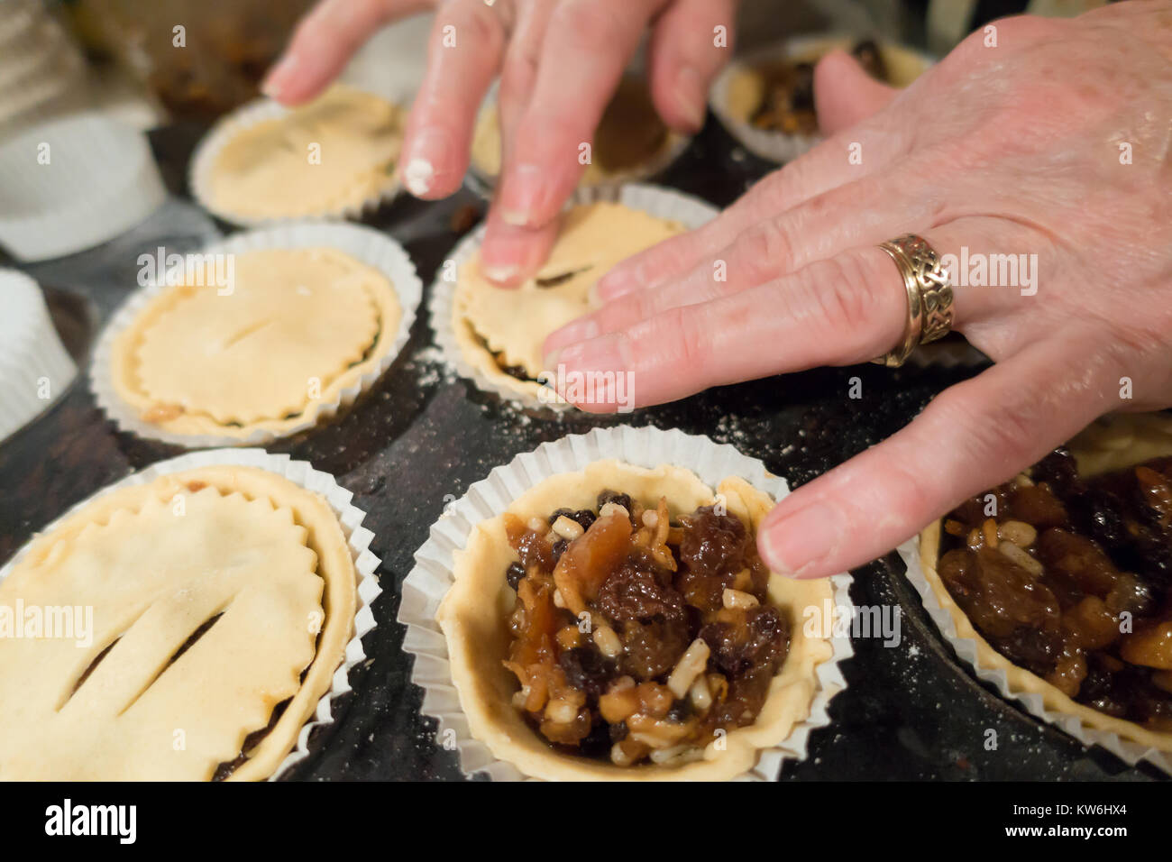 making-mince-pies-ladies-hands-place-circles-on-pasty-ontop-of-pies-KW6HX4.jpg