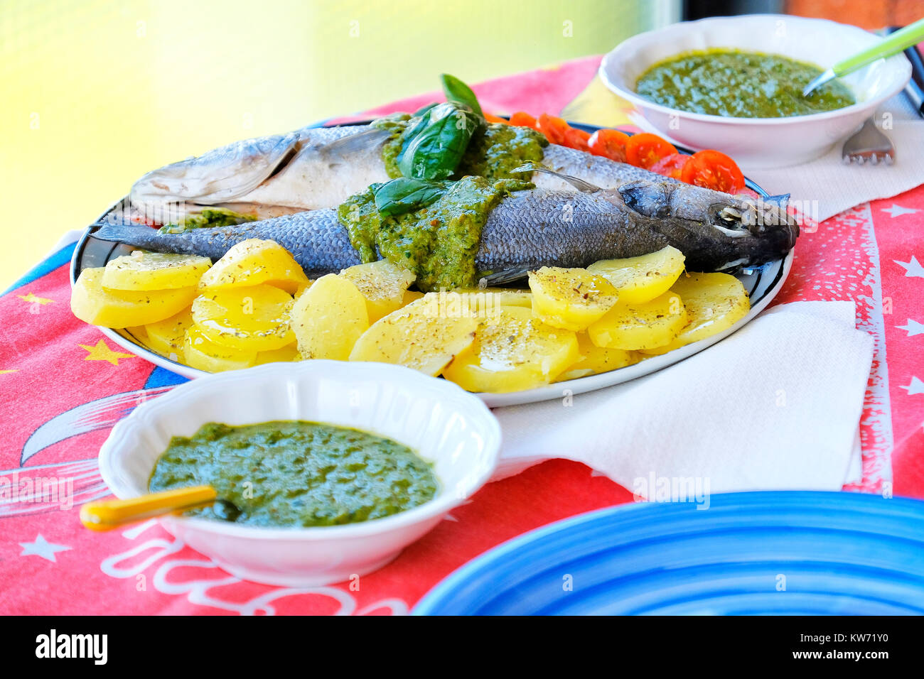 european sea bass branzino steaming potatoes tomatoes basil sauce recipe - Stock Image