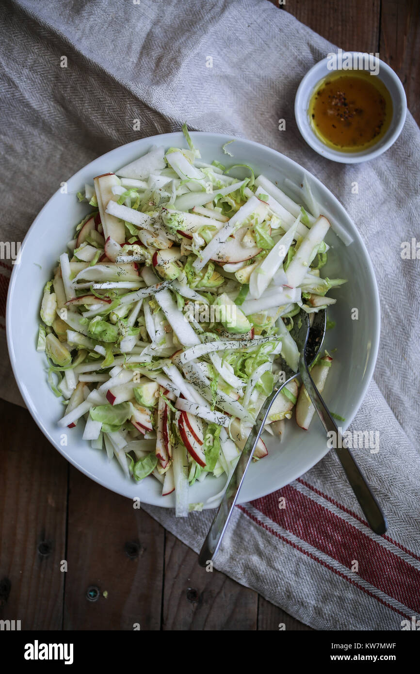 Fresh healthy vegan salad with fennel, brussels sprout, apples, celery, white turnip. With spicy citronette and - Stock Image