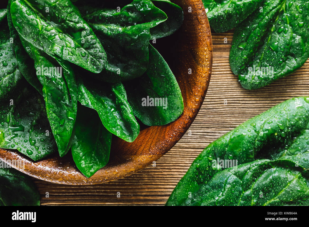 Freshly Washed Spinach Leaves in Teak Bowl on Cedar Wood Table - Stock Image