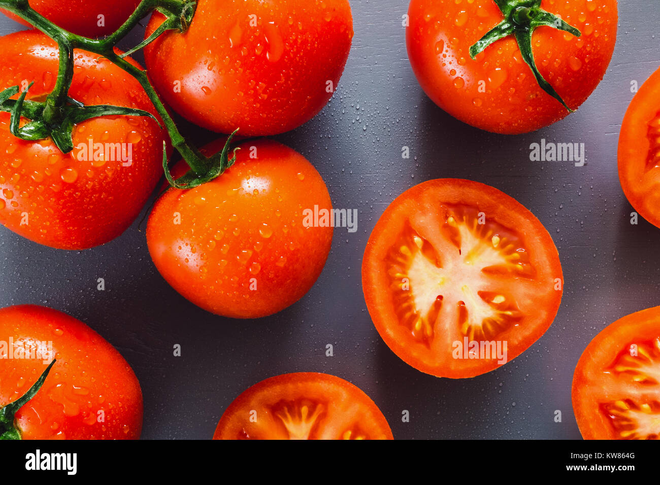 Freshly Washed and Sliced Tomatoes on Blue Table - Stock Image