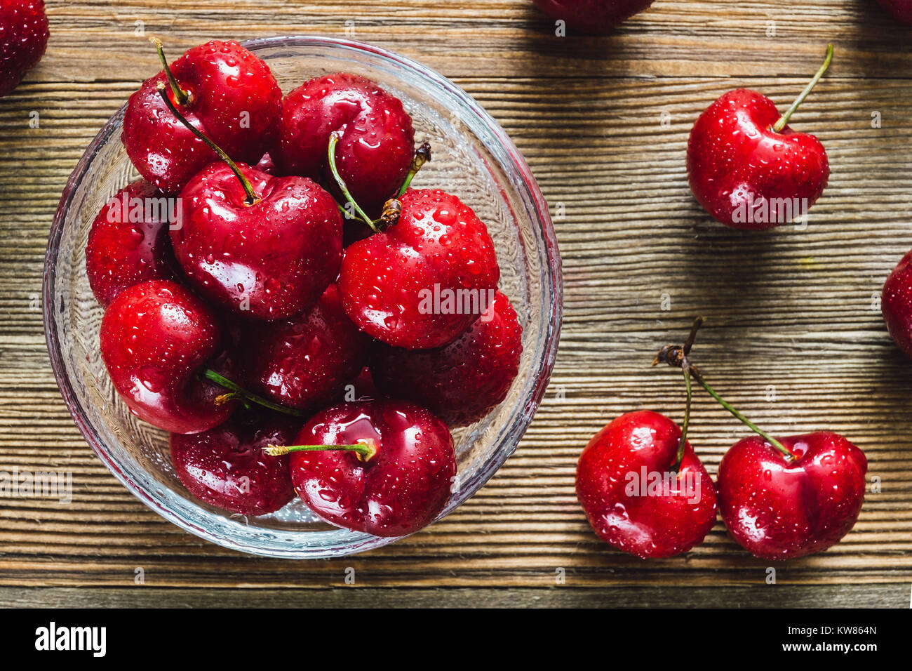 Freshly Washed Cherries in Glass Bowl on Cedar Table - Stock Image