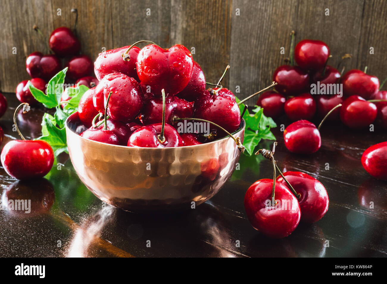 Copper Bowl of Fresh Cherries on Dark Table with Ivy - Stock Image