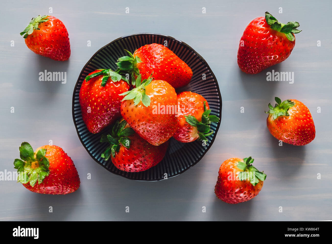 Bowl of Strawberries on Grey Table - Stock Image