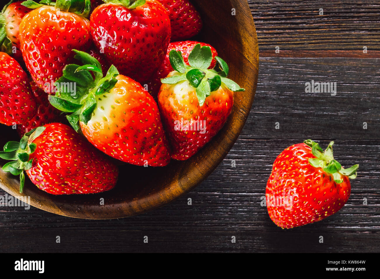 Bowl of Fresh Strawberries on Dark Table - Stock Image