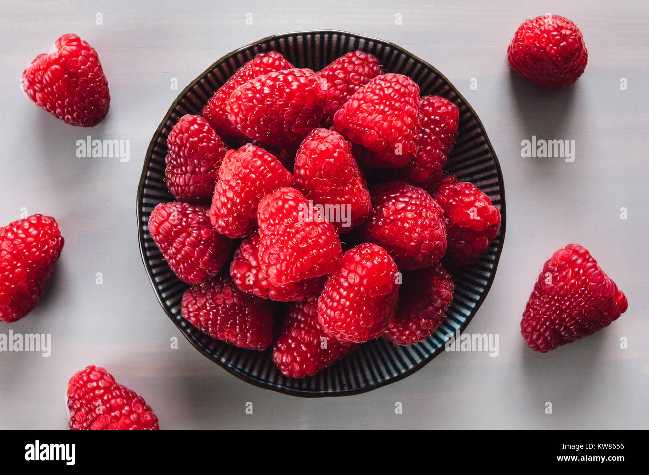 Bowl of Fresh Raspberries on Grey Table - Stock Image