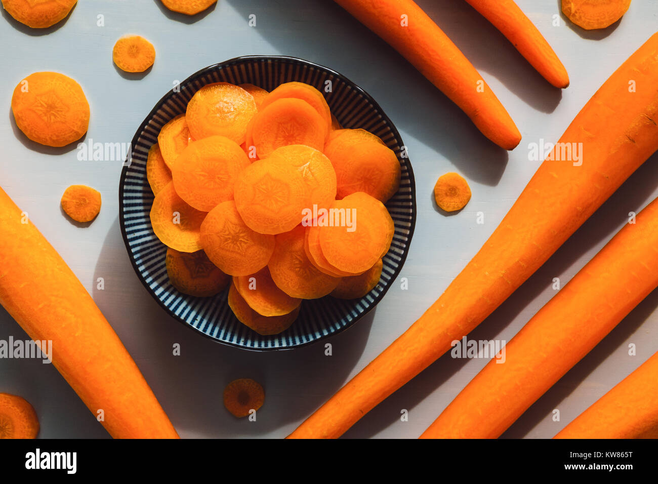 Peeled and Sliced Carrots on Grey Table - Stock Image
