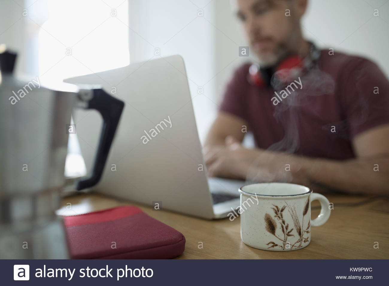 Steaming cup of coffee and man telecommuting,working at laptop - Stock Image