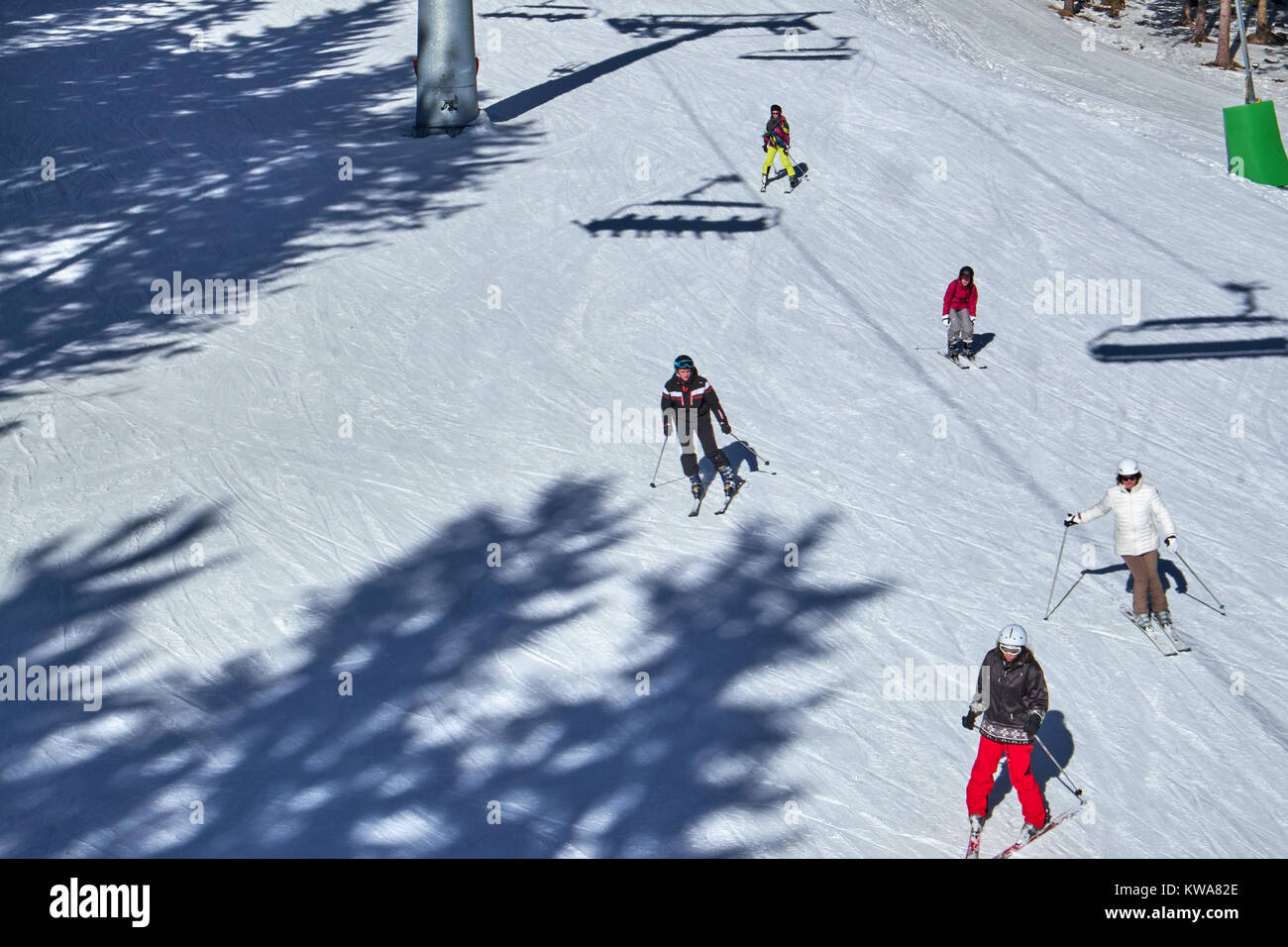 WINTERBERG, GERMANY - FEBRUARY 14, 2017: Group of skiers running under a chairlift at Ski Carousel Winterberg - Stock Image