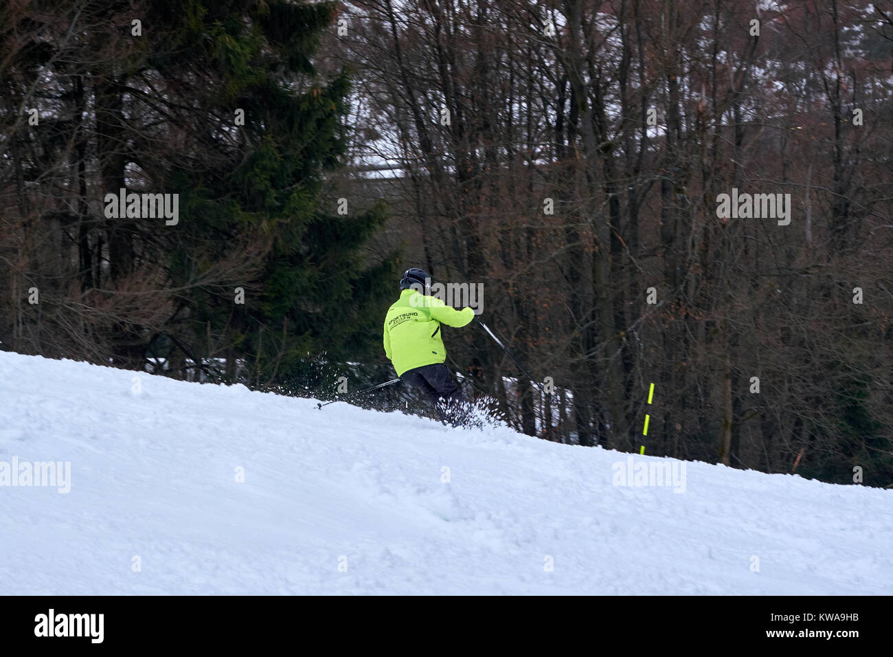 WINTERBERG, GERMANY - FEBRUARY 16, 2017: Man in fluorescent jacket taking a swing on a piste at Ski Carousel Winterberg - Stock Image