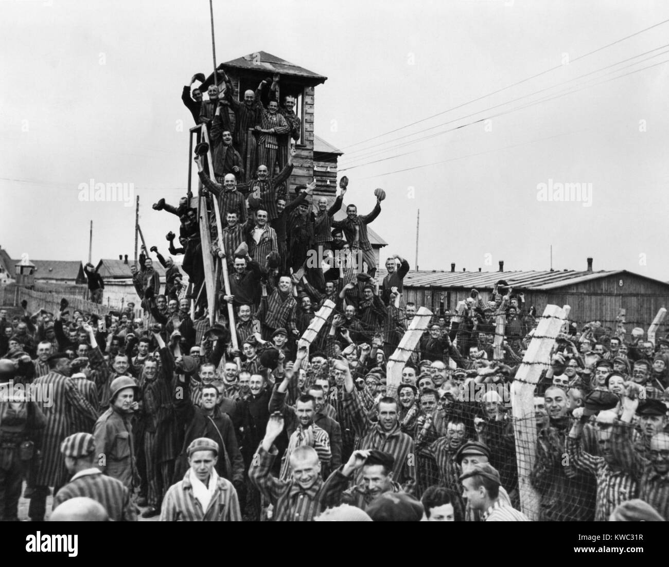 Dachau Prisoners wave and cheer the Seventh US Army liberators. April 29, 1945, World War 2 (BSLOC_2015_13_18) - Stock Image