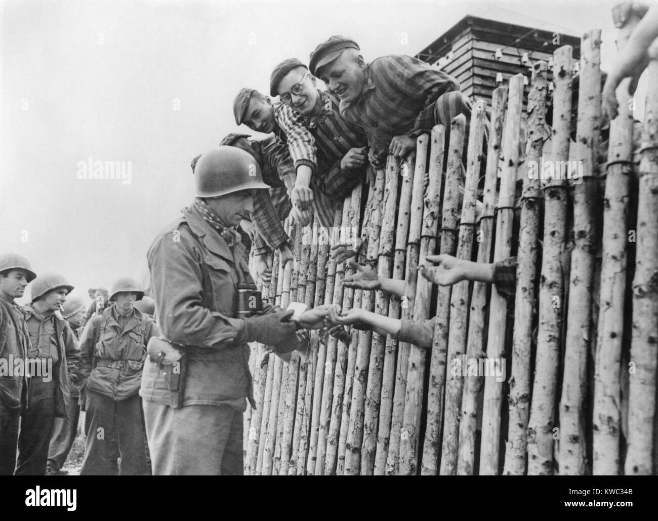 GI of the Seventh US Army gives his last cigarettes to liberated Dachau prisoners behind a stockade. April 29, 1945, - Stock Image