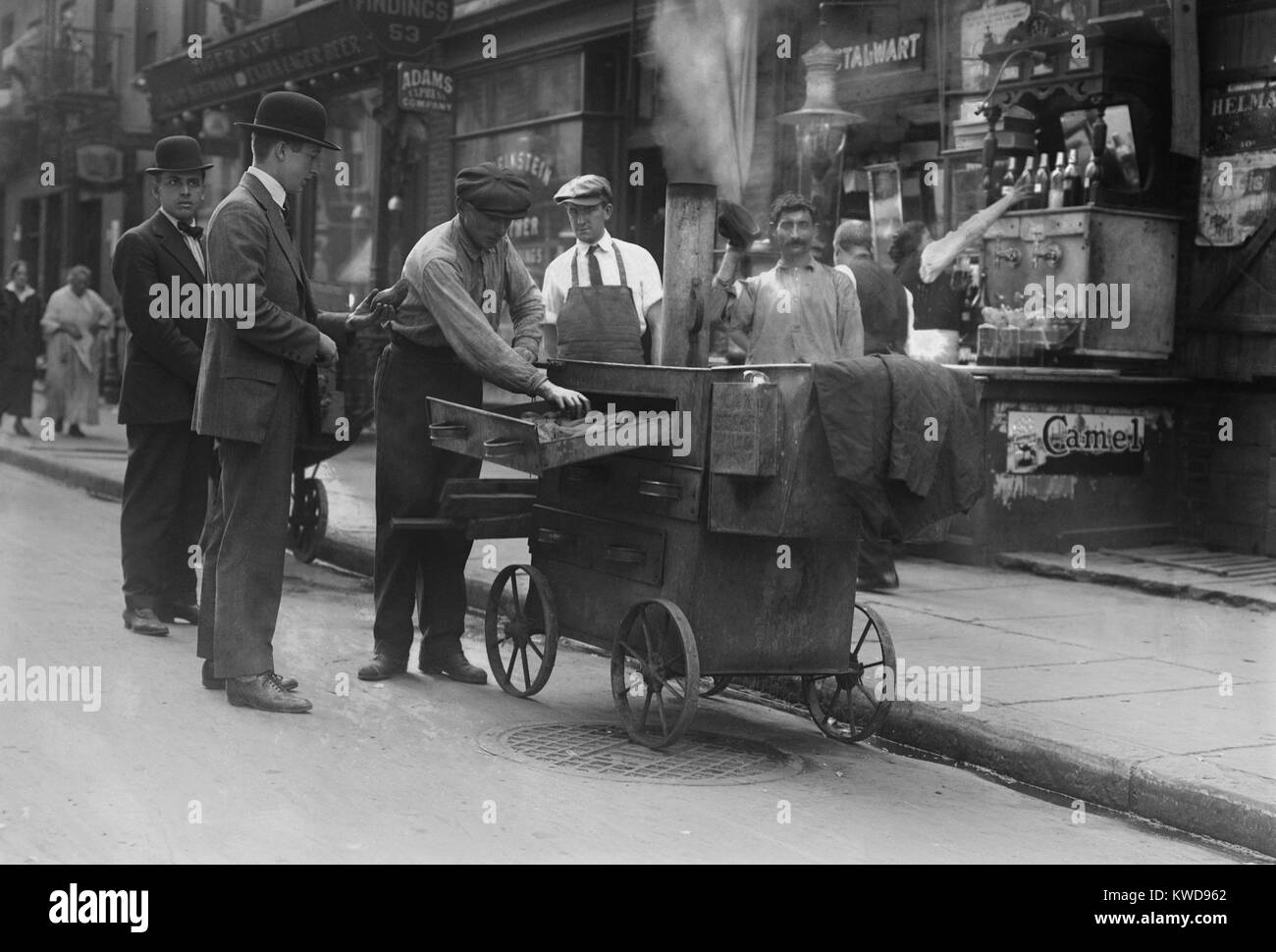 Baked potato vendor with a pushcart oven in New York's Lower East Side, c. 1915-20. The neighborhood was packed - Stock Image
