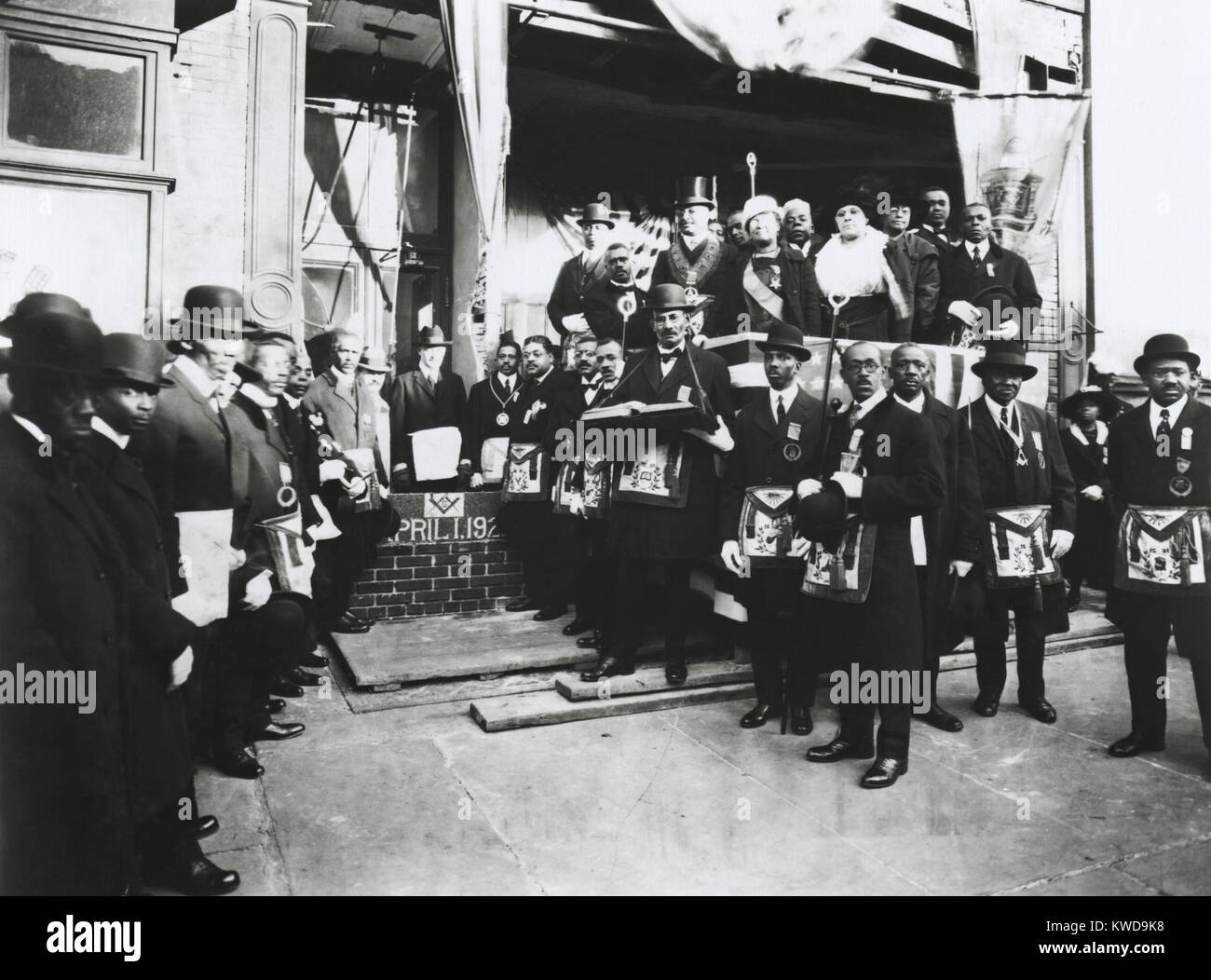 Arthur Alfonso Schomburg in a group of Masons and Odd Fellows, April 1, 1922. He is standing in front of brick wall, - Stock Image