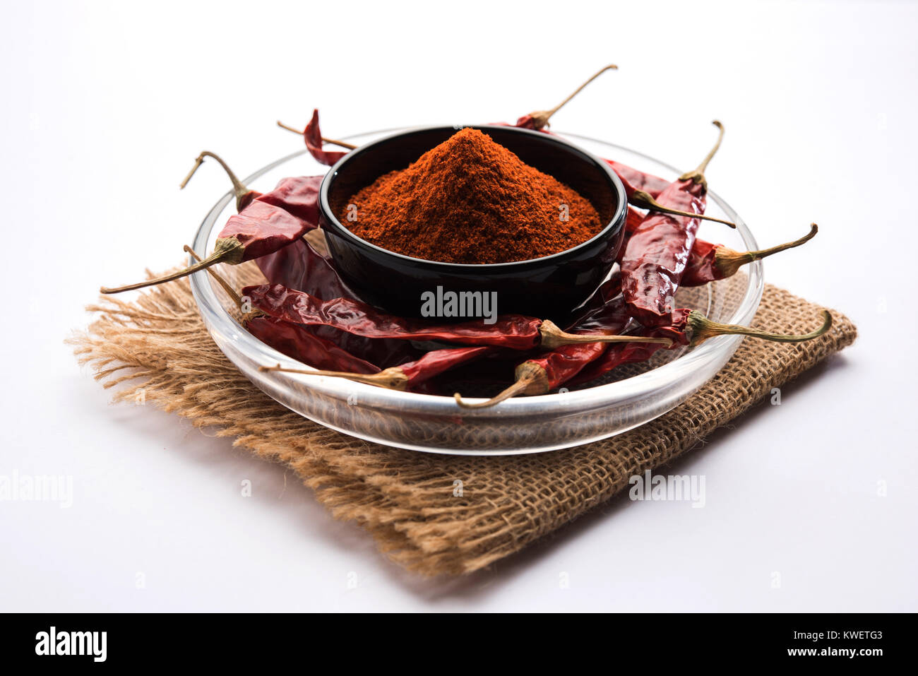 Red Chilly Powder in a bowl with dried red chillies over colourful background or pile of red chilli powder over - Stock Image