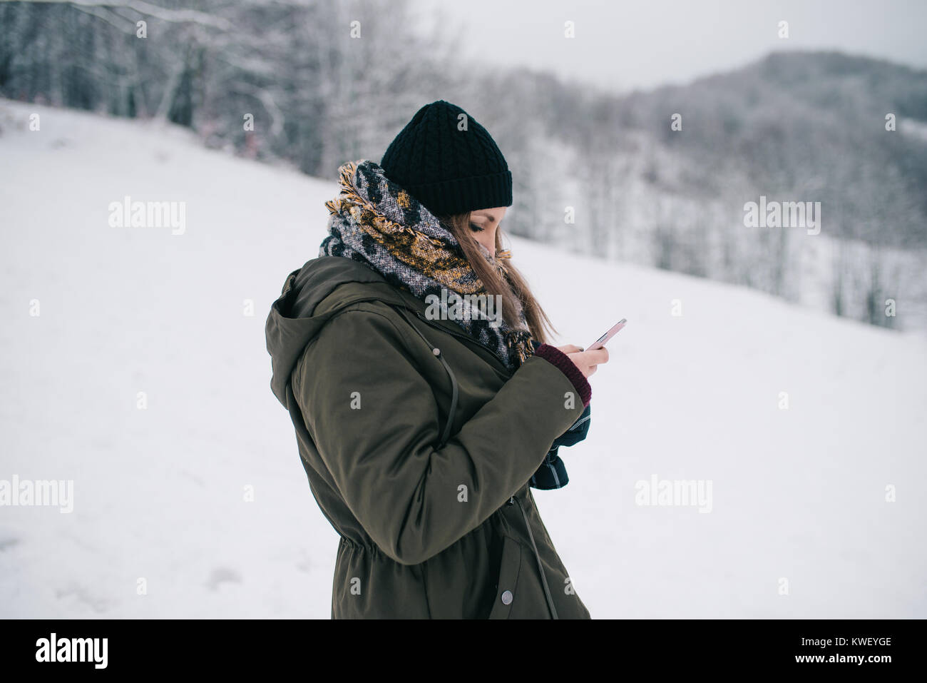 Woman using mobile smartphone outdoor in winter - Stock Image