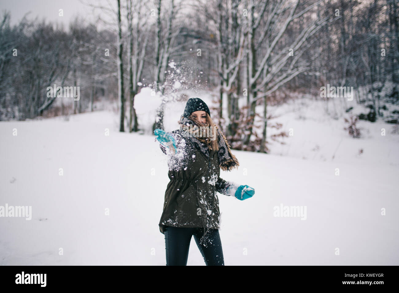 Happy woman throwing snowball - Stock Image