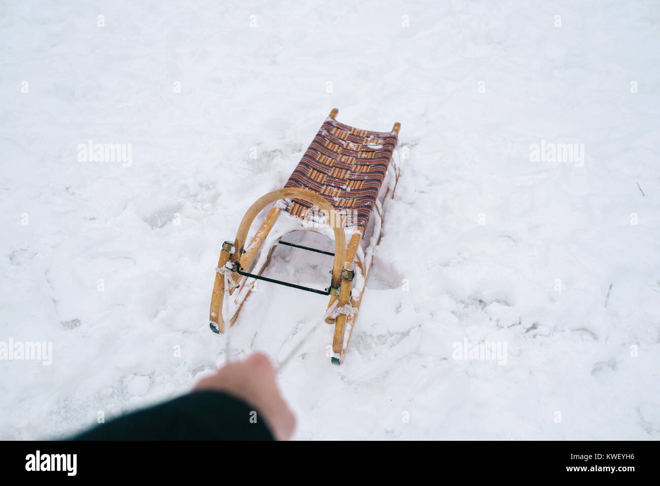 Detail of hand pulling sled. First person view. - Stock Image