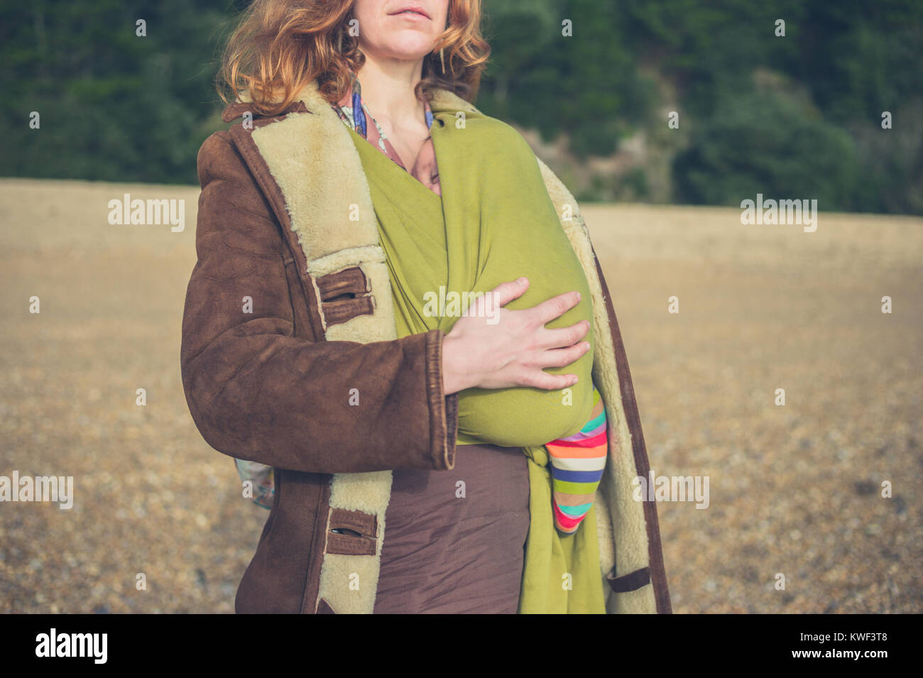 A young mother is standing on the beach with her baby in a sling on a winter day - Stock Image
