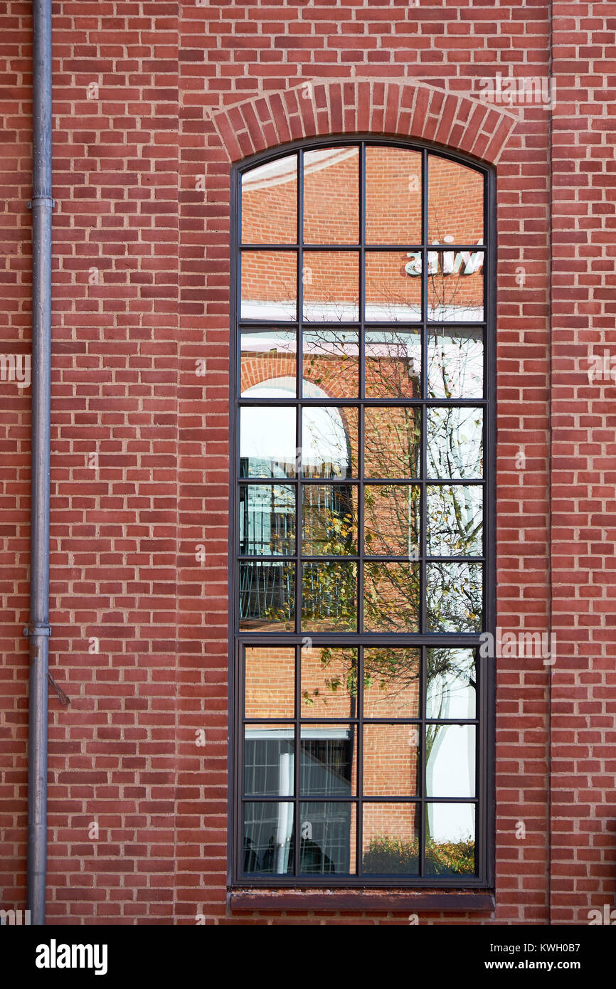 Tall arch format metal barn style window with small glazing pattern, in a red brick facade - Stock Image