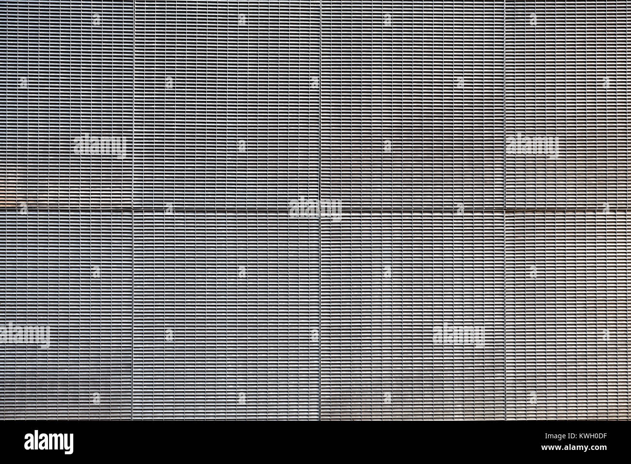 Building facade covered in galvanised metal grills - Stock Image